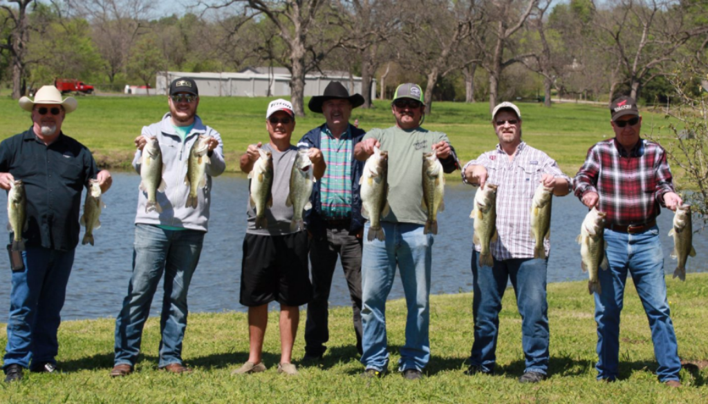 Trophies from the Celebrity Fishing Tournament are proudly being held up by all the winners.